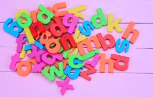 Group of colorful letters on purple table